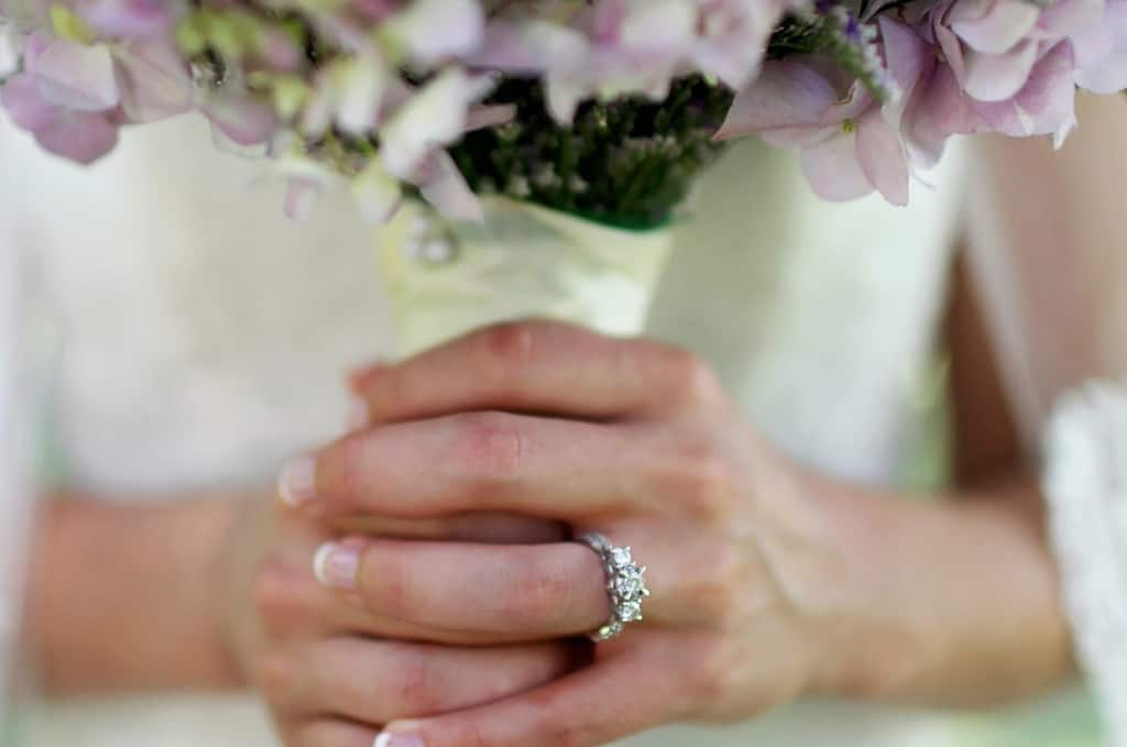 a bride with three stone ring and flowers